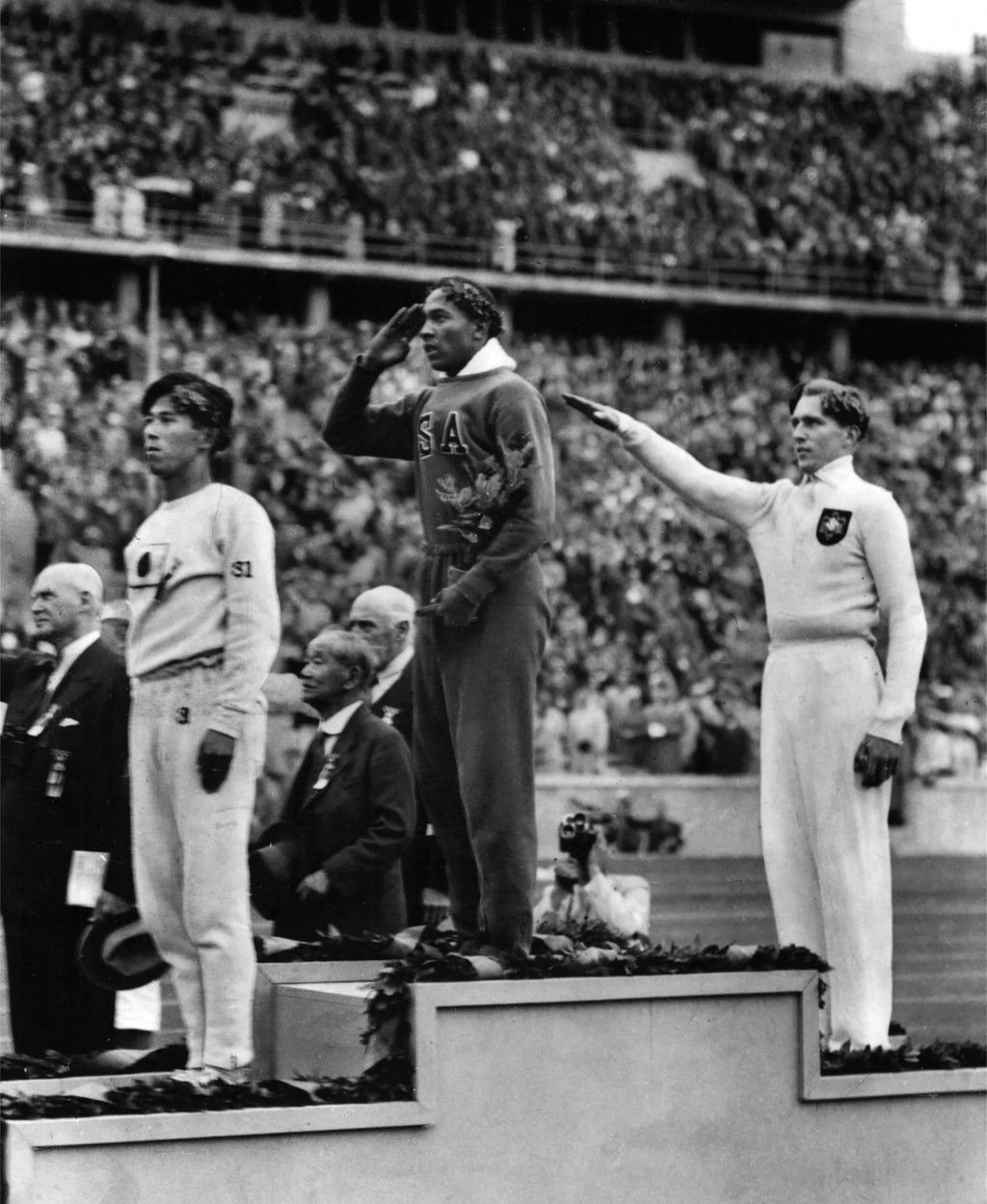 FILE - In this Aug. 11, 1936, file photo, America's Jesse Owens, center, salutes during the presentation of his gold medal for the long jump, after de...