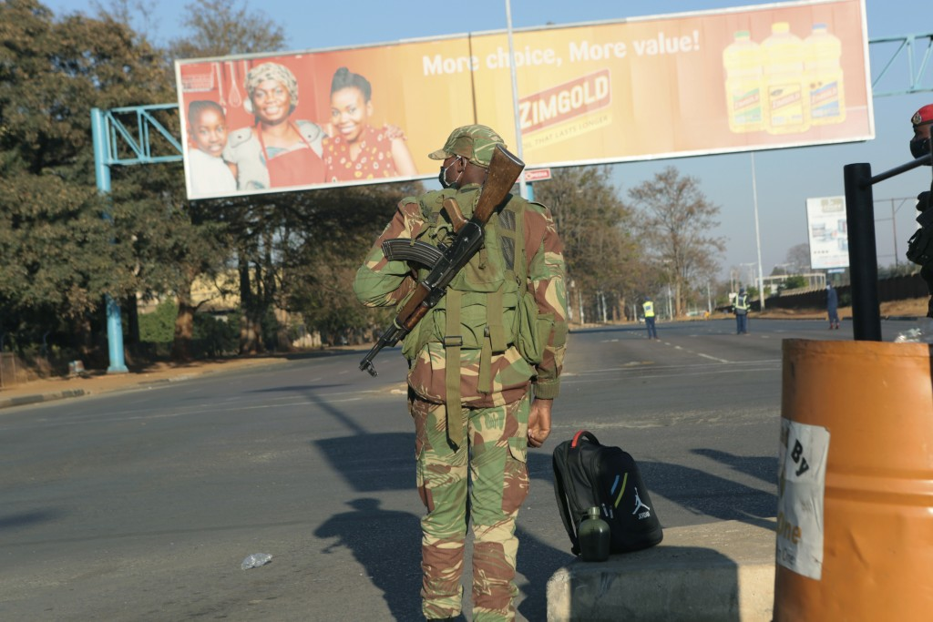 An armed soldier stands on a deserted street in Harare, Friday, July, 31, 2020. Zimbabwe's capital, Harare, was deserted Friday, as security agents vi...