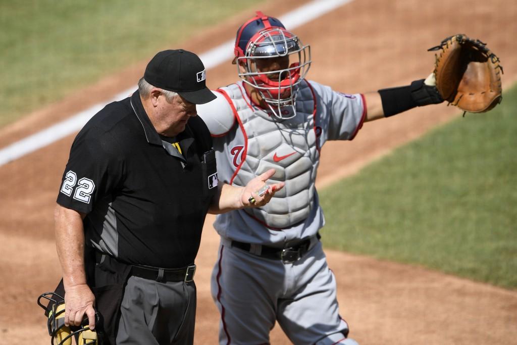 Washington Nationals catcher Kurt Suzuki, right, signals for assistance after umpire Joe West (22) was injured during the first inning of a baseball g...