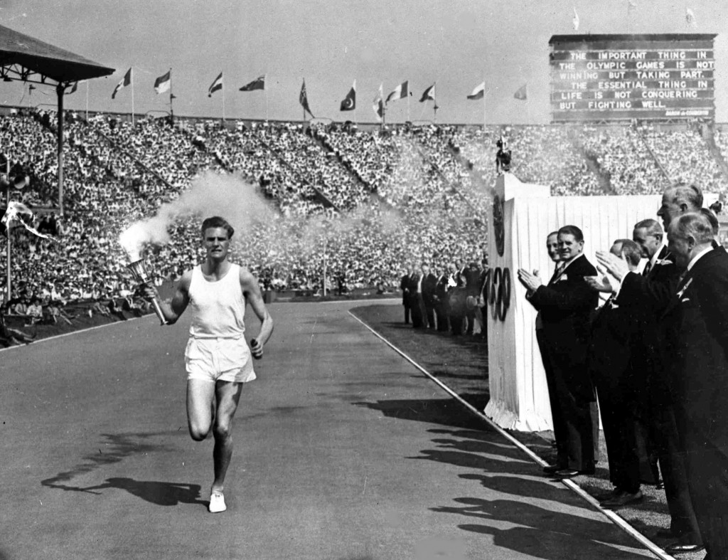 FILE - In this July 29, 1948 file photo, British athlete John Mark holds the Olympic Flame aloft as he makes his circuit of the Olympic track during t...