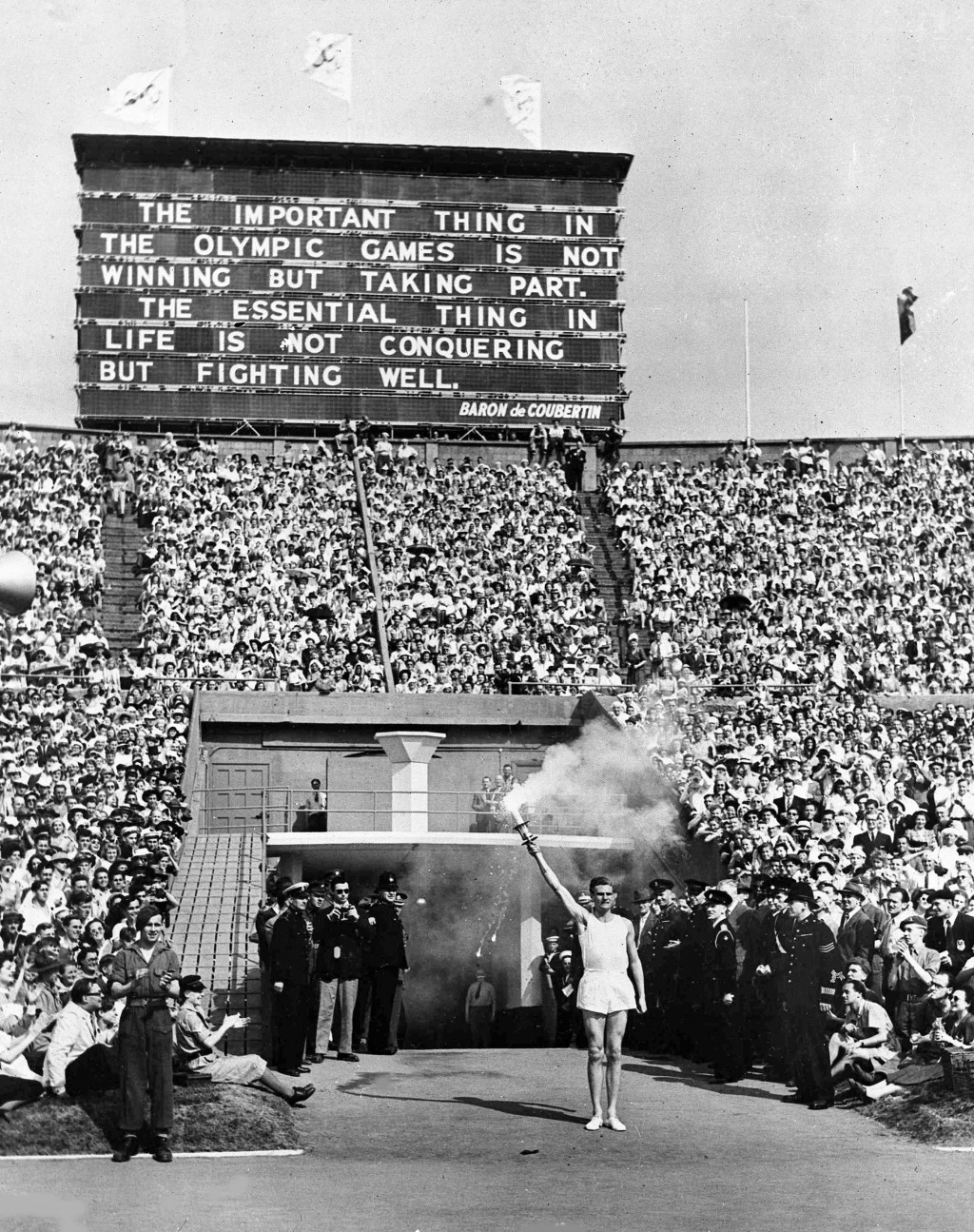 FILE - In this July 29, 1948 file photo, British athlete John Mark holds the Olympic Flame aloft in salute, beneath a quotation from Baron Pierre de C...