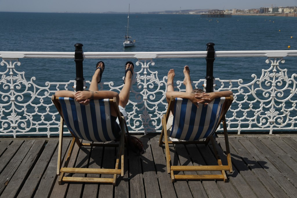 Two people relax in deck chairs as beachgoers enjoy the sunshine and sea on what is now Britain's hottest day of the year so far, in Brighton, England...