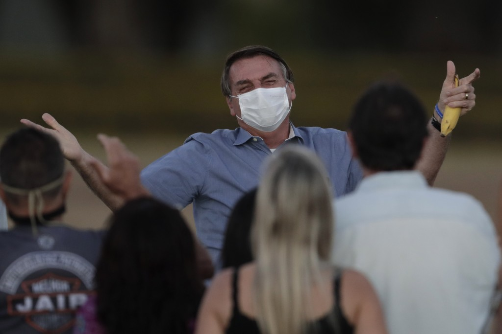 Brazil's President Jair Bolsonaro, who is infected with COVID-19, wears a protective face mask as he talks with supporters during a Brazilian flag ret...