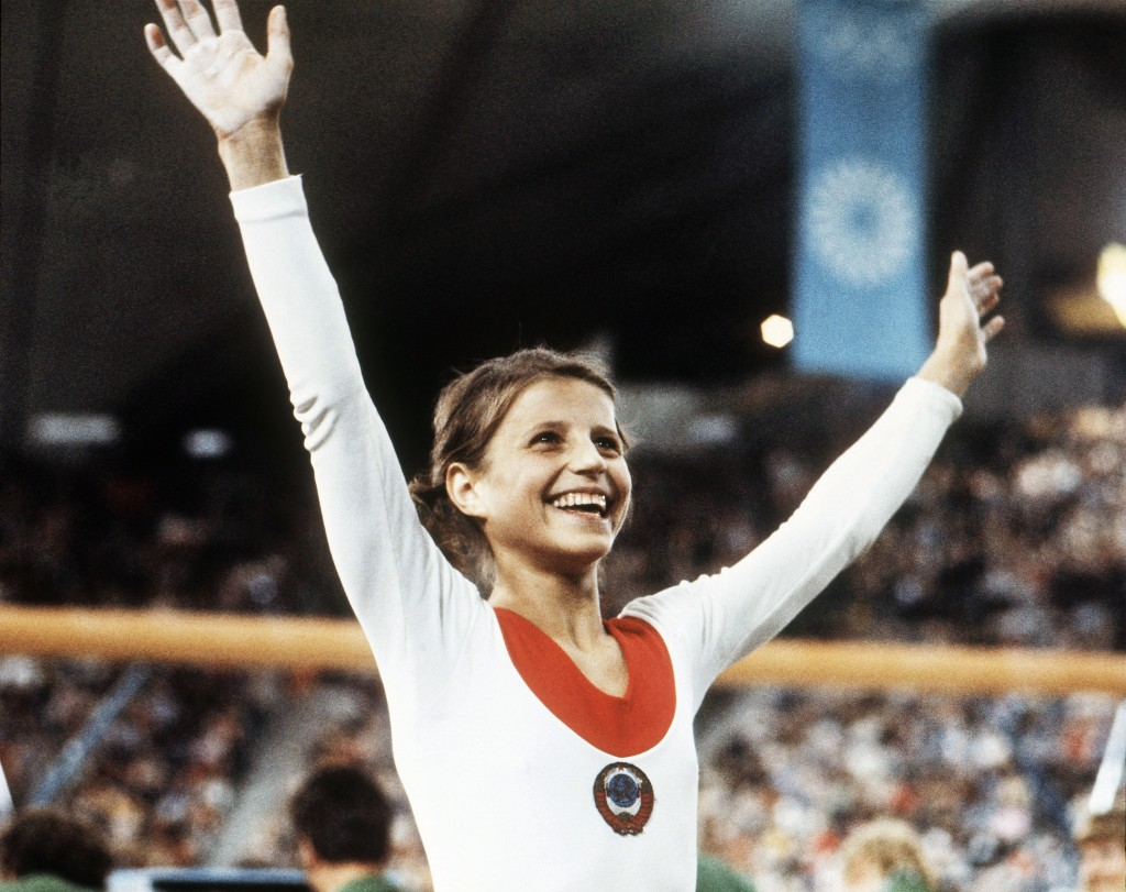 FILE - In this Aug. 1972, file photo, Olga Korbut, of Russia, throws up her arms in joy after winning the Individual Women's Gymnastic event at the 19...