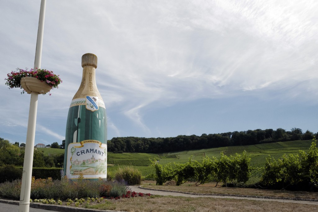 A Champagne advert is displayed at the entrance of the village in Avize, in the Champagne region, east of Paris, Tuesday, July 28, 2020. Producers in ...