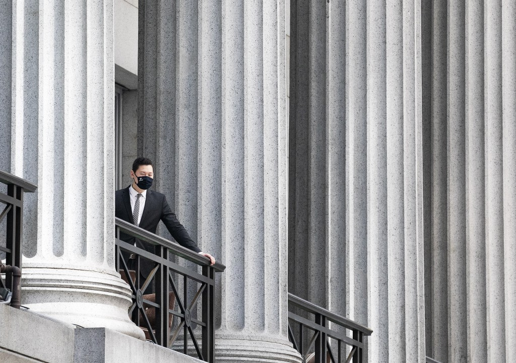 A man standing on a balcony overlooks Wall Street, Thursday, July 30, 2020, in New York. Stocks are falling on Wall Street Thursday after reports show...