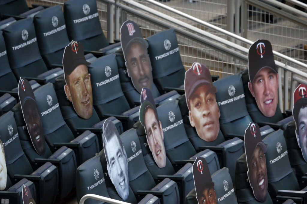 Cardboard faces, including some athletes and others, adorn seats behind home plate at Target Field as the Minnesota Twins host the Cleveland Indians i...
