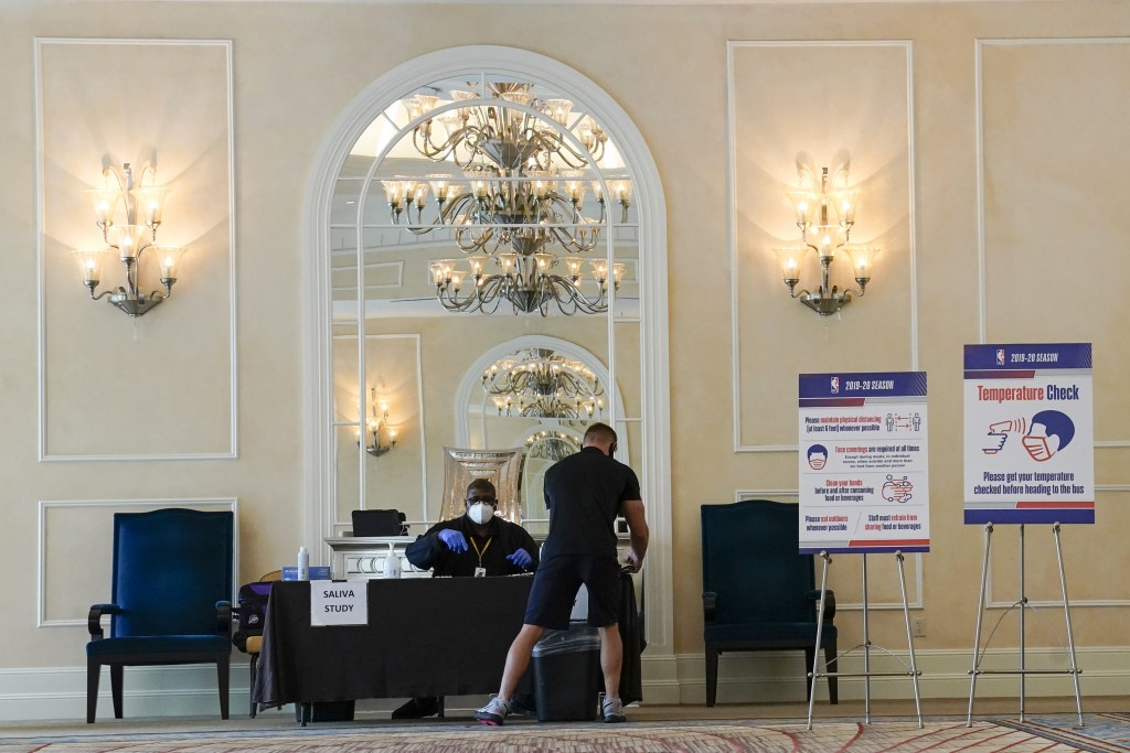 A man gets tested for COVID-19 at an NBA basketball testing site Wednesday, July 29, 2020, in Orlando, Fla. As coronavirus cases surge in hard-hit Flo...