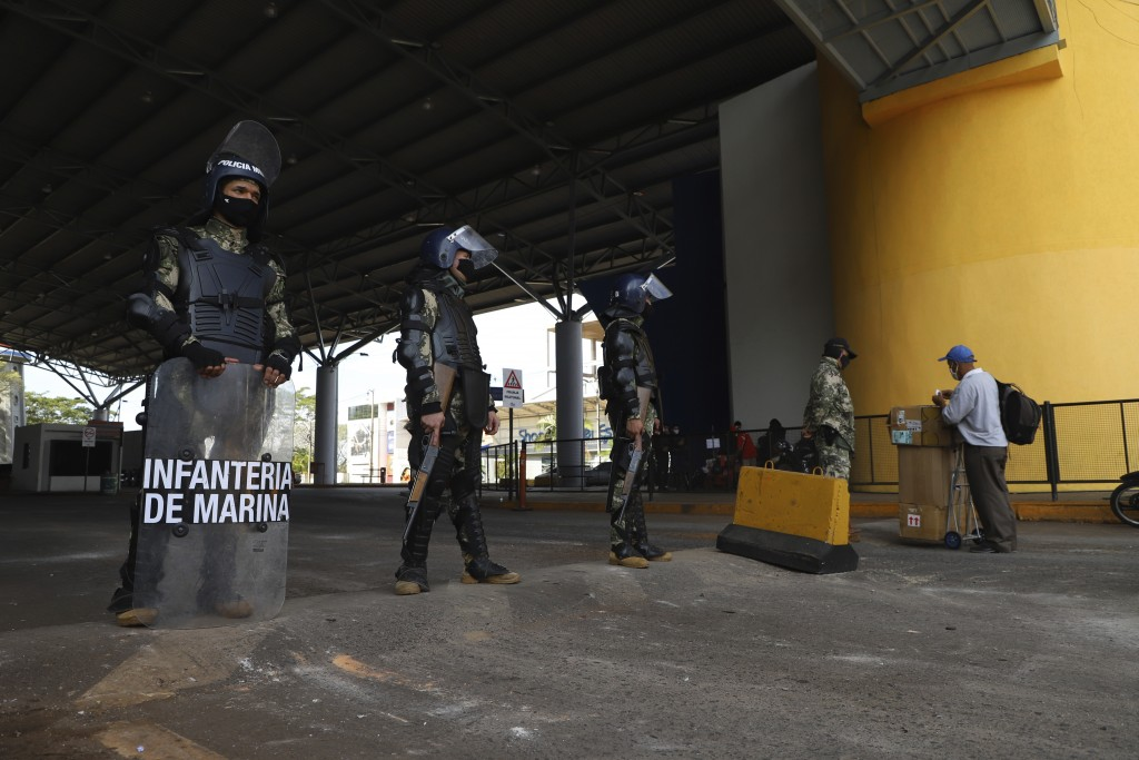 Navy marines stand guard at the entrance of Friendship Bridge that connects Ciudad Del Este, Paraguay, and Brazil's For do Iguazu, Thursday, July 30, ...