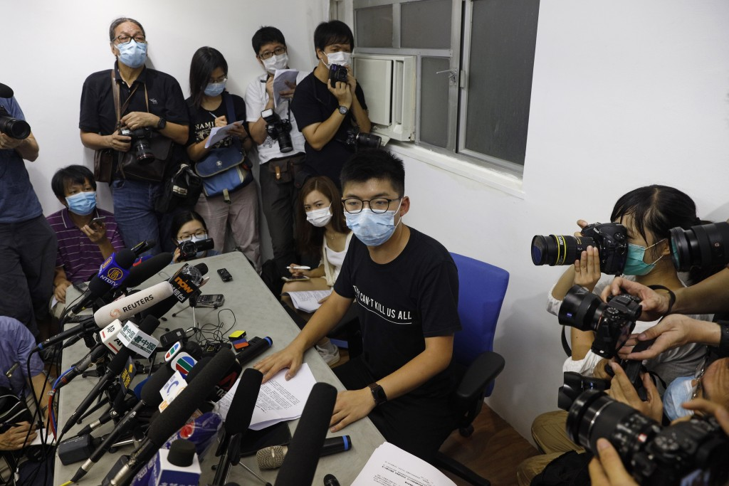 Hong Kong pro-democracy activist Joshua Wong, center, attends a press conference in Hong Kong, Friday, July 31, 2020. On Thursday, 12 pro-democracy ca...
