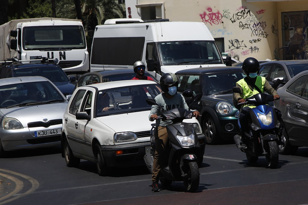 Motorcyclists wear face masks in capital Nicosia, Cyprus, Friday, July 31, 2020. Cyprus has made mask-wearing compulsory in all indoor areas where peo...