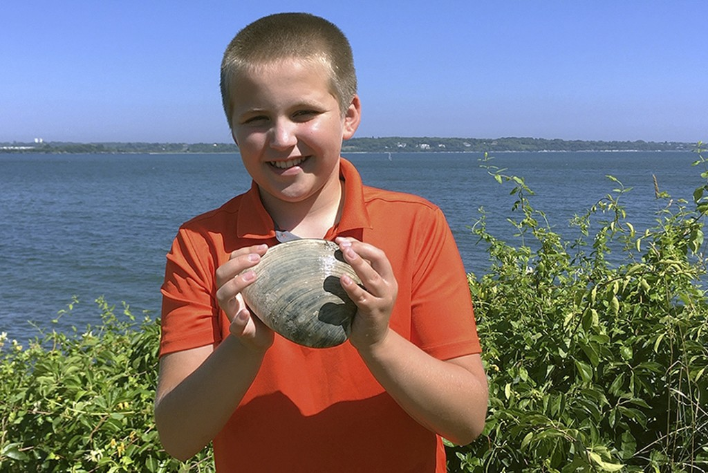 In this Tuesday, July, 28, 2020, photo provided by the University of Rhode Island, Cooper Monaco holds the large quahog he found Monday while clamming...