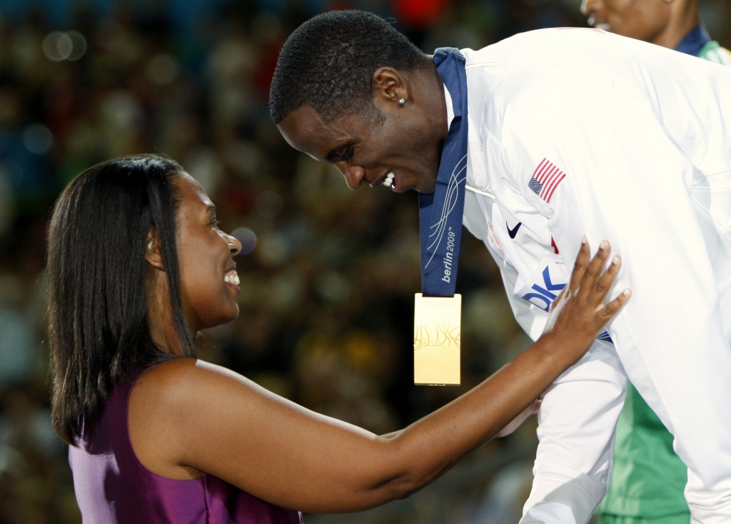 FILE - In this Aug. 22, 2009, file photo, United States' Dwight Phillips, right, receives his gold medal from Jesse Owens' granddaughter, Marlene Dort...