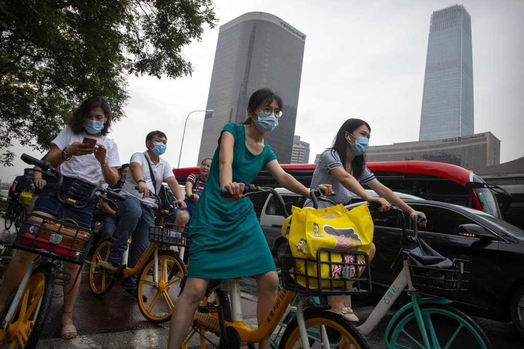 People wearing face masks to protect against the coronavirus wait at an intersection in the central business district in Beijing, Friday, July 31, 202...