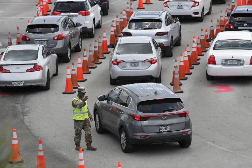 FILE - In this July 8, 2020, file photo, National Guardsman directs traffic at a COVID-19 testing site outside Hard Rock Stadium, in Miami Gardens, Fl...