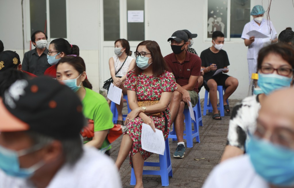 People wait in line to be tested for COVID-19 in Hanoi, Vietnam on Friday, July 31, 2020. Vietnamese state media on Friday reported the country's firs...