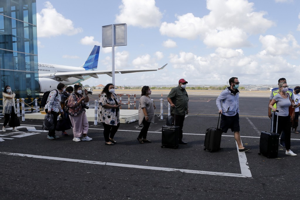 Passengers walk with a social distancing on their arrival at Bali airport, Indonesia on Friday, July 31, 2020. Indonesia's resort island of Bali reope...