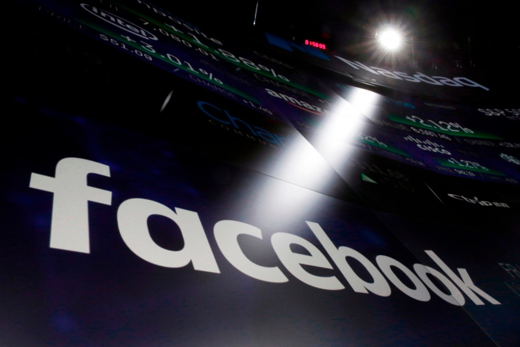 FILE- In this March 29, 2018, file photo, the logo for Facebook appears on screens at the Nasdaq MarketSite in New York's Times Square.  Big Tech comp...