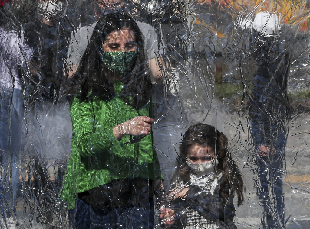 A woman and child wearing protective face masks prepare to enter a decontamination chamber as a precaution against the spread of the new coronavirus, ...