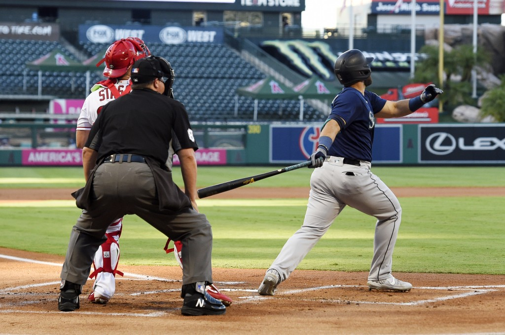 Seattle Mariners' Jose Marmolejos, right, hits a three-run home run as Los Angeles Angels catcher Max Stassi, left, watches along with home plate umpi...