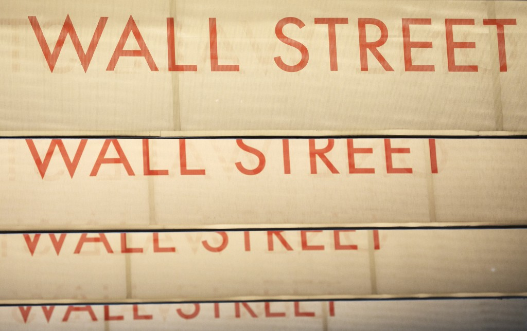 Signs for Wall Street are shown, Thursday, July 30, 2020, in New York. Stocks are falling on Wall Street Thursday after reports showed that layoffs ar...