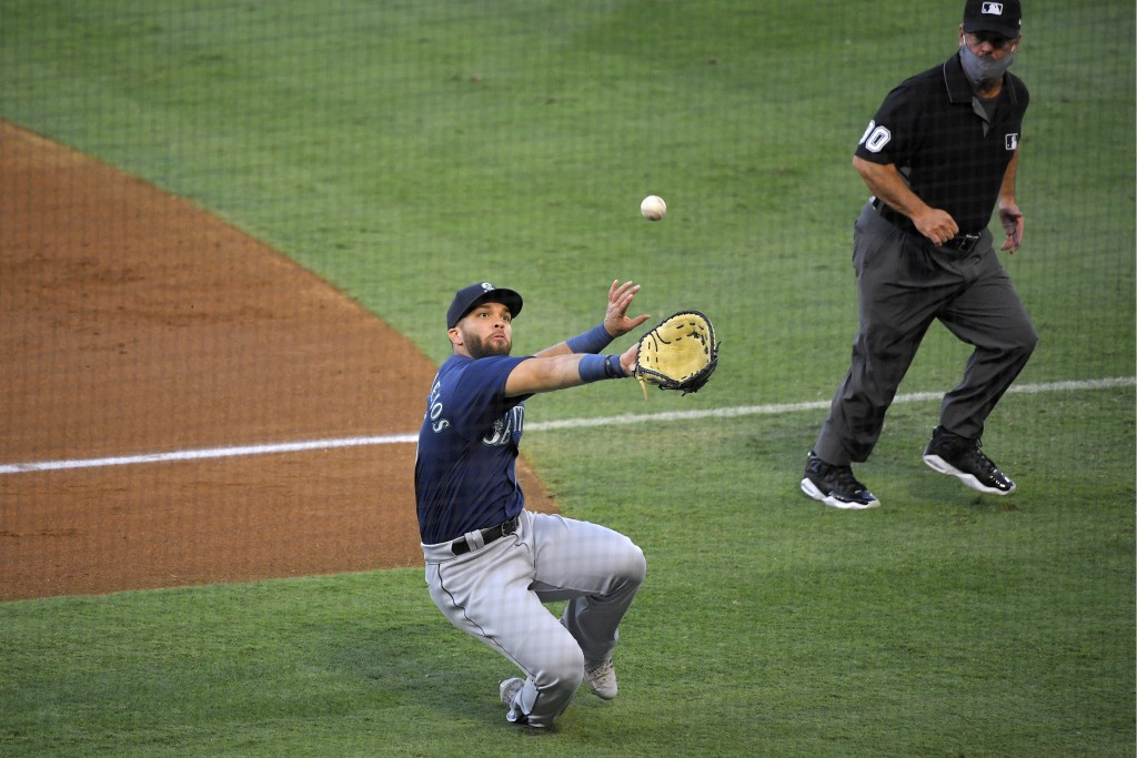 Seattle Mariners first baseman Jose Marmolejos can't get to a foul ball hit by Los Angeles Angels' Anthony Rendon during the first inning of a basebal...