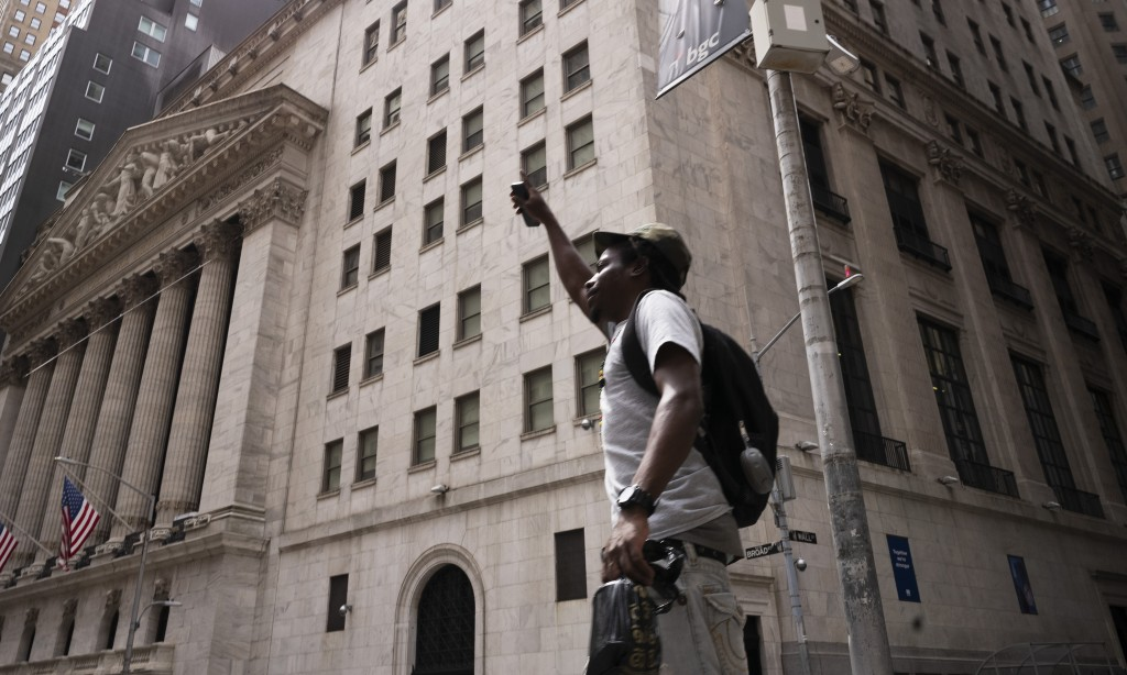 A man lifts his arm as he walks by the New York Stock Exchange, Thursday, July 30, 2020. Stocks are falling on Wall Street Thursday after reports show...