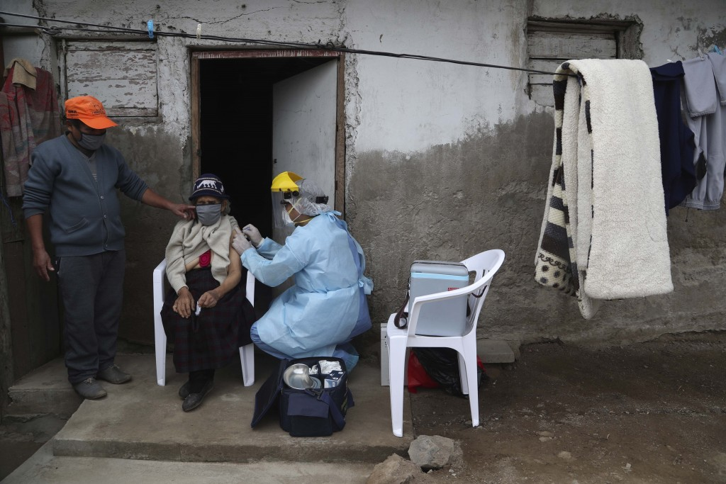 Victoria Melgar, 92, gets a flu shot in the El Agustino neighborhood of Lima, Peru, Thursday, July 30, 2020.  In the middle of winter, medical personn...