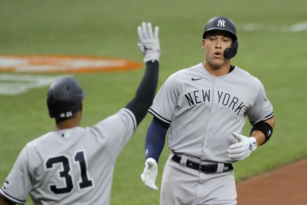 New York Yankees' Aaron Judge, right, is greeted at home by Aaron Hicks (31) after scoring on a single by Giancarlo Stanton off Baltimore Orioles star...