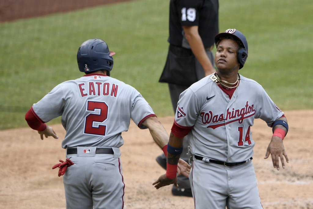 Washington Nationals' Starlin Castro (14) celebrates with Adam Eaton (2) after both scored on a double by Kurt Suzuki during the third inning of the t...