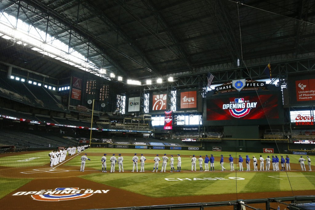 Arizona Diamondbacks players and coaches, left, stand along with Los Angeles Dodgers players and coaches, right, prior to a the Diamondbacks' opening ...