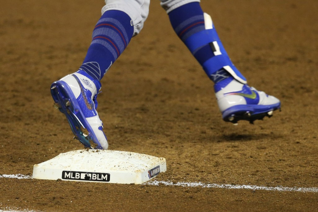 "Los Angeles Dodgers' Mookie Betts rounds first base on a single against the Arizona Diamondbacks as the MLB and BLM for ""Black Lives Matter"" logos ado..."
