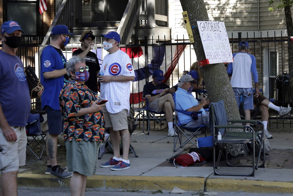 Chicago Cubs fans wait for a ball outside of Wrigley Field before the Opening Day baseball game between the Chicago Cubs and the Milwaukee Brewers in ...