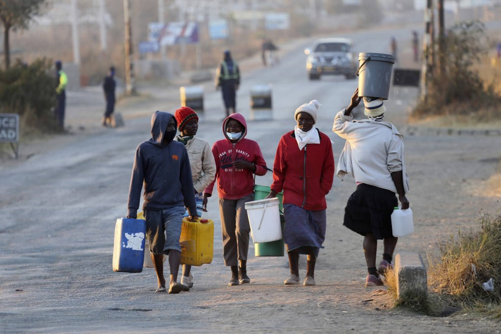 People carry buckets to fetch water past a police checkpoint in Harare, Friday, July, 31, 2020. Zimbabwe's capital, Harare, was deserted Friday, as se...