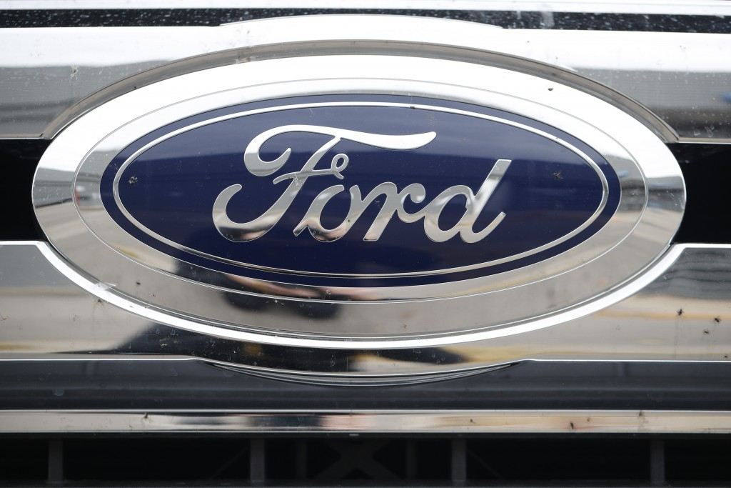 FILE - In this  Oct. 20, 2019 file photograph, the company logo shines off the grille of an unsold 2019 F-250 pickup truck at a Ford dealership in Lit...