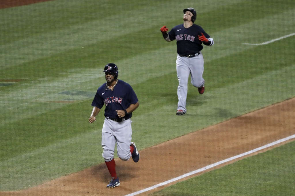 Christian Vazquez, right, and Xander Bogaerts celebrate as they approach home plate after Bogaerts hit a two-run homer run during the fourth inning of...