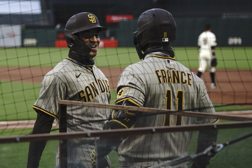San Diego Padres' Trent Grisham, left, is congratulated by Ty France after scoring against the San Francisco Giants during the fourth inning of a base...