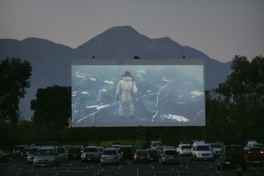 FILE - Moviegoers watch a movie preview at Mission Tiki drive-in theater in Montclair, Calif., on May 28, 2020. About 1,000 theaters in the U.S. are c...