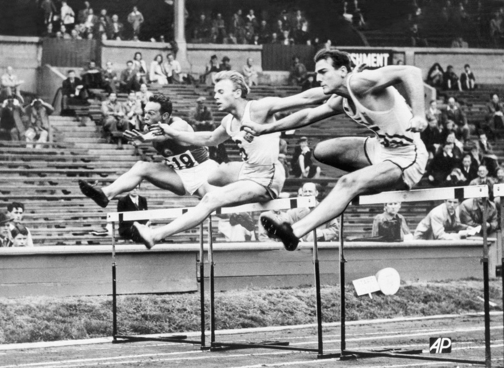 FILE - In this Aug. 7. 1948 file photo, Bob Mathias, right, is shown during the Olympic decathlon in London. At left is Oto Rebula of Yugoslavia and a...