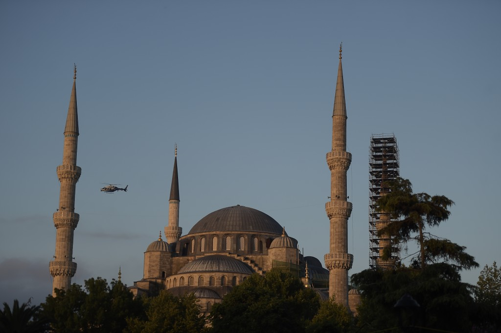 A police helicopter patrols above the iconic Sultan Ahmed Mosque, better known as the Blue Mosque, on the historic Sultanahmet district in Istanbul, d...