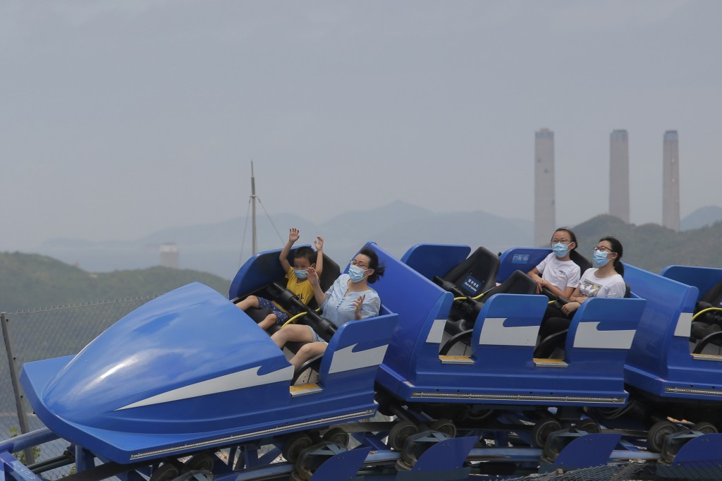 Guests wearing face masks to prevent the spread of the new coronavirus, ride on a roller coaster at Ocean Park in Hong Kong Saturday, June 13, 2020. I...