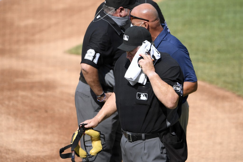 Home plate umpire Joe West, foregroundr, is led off the field after he was injured during the first inning of a baseball game between the Toronto Blue...