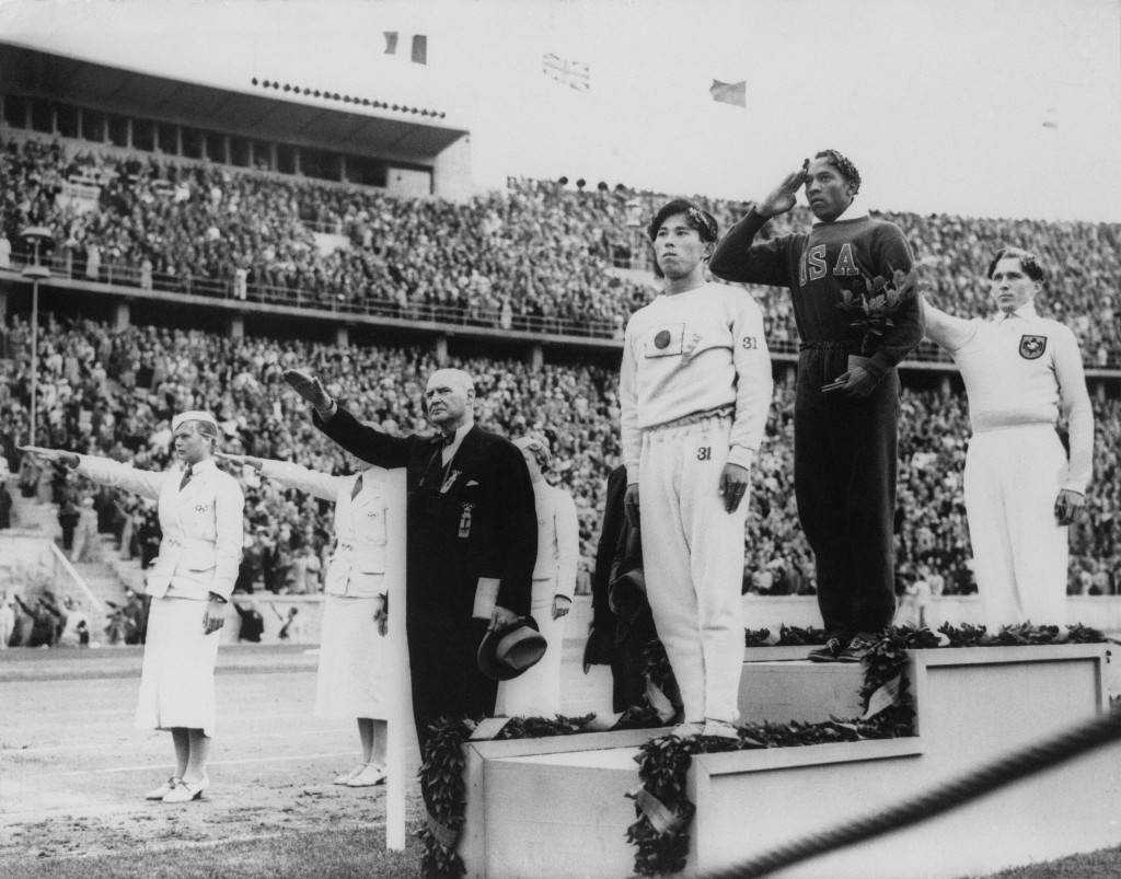 FILE - In this Aug. 11, 1936, file photo, America's Jesse Owens, second from right, salutes during the presentation of his gold medal for the long jum...