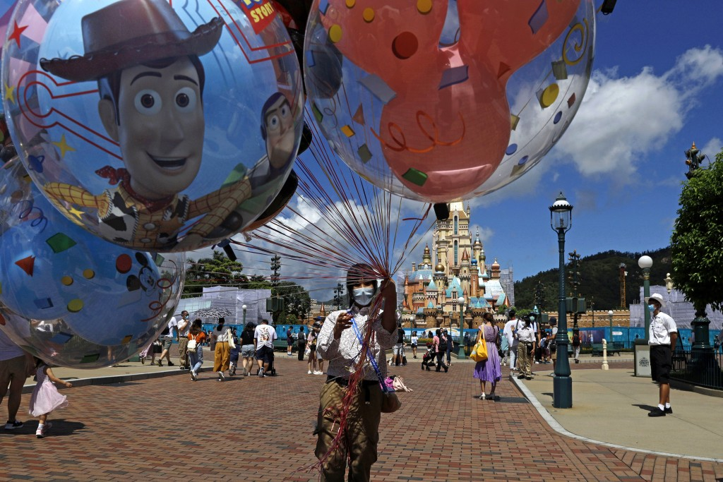 An employee wearing a face mask to prevent the spread of the new coronavirus, sells balloons at the Hong Kong Disneyland Thursday, June 18, 2020. In M...