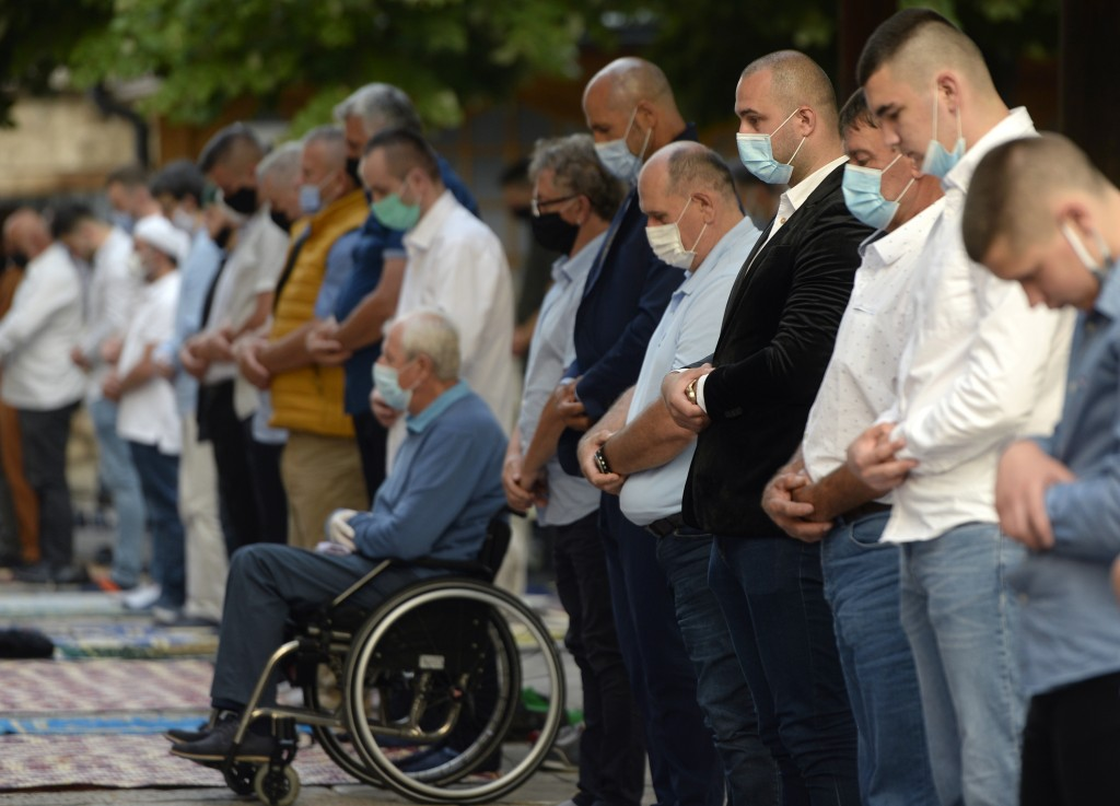 Worshippers wearing masks to help stop the spread of the coronavirus, offer Eid al-Adha prayer in front of the Gazi Husrev-beg mosque in Sarajevo, Bos...