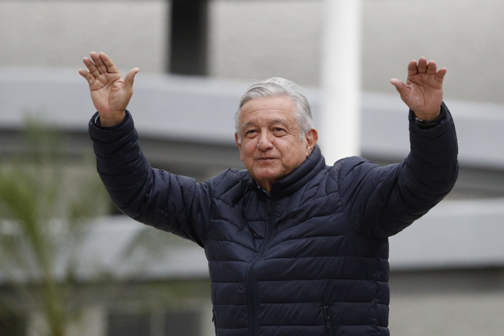 FILE - In this April 3, 2020 file photo, Mexican President Andres Manuel Lopez Obrador waves to supporters at the end of a visit to a Social Security ...
