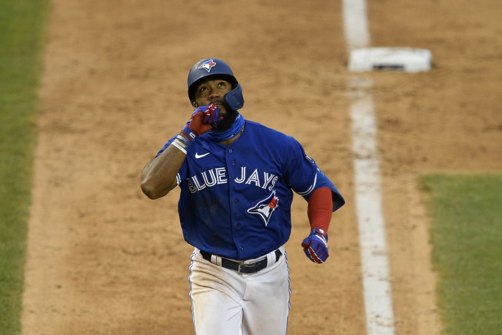 Toronto Blue Jays' Teoscar Hernandez reacts as he heads home on his home run during the eighth inning of a baseball game against the Washington Nation...
