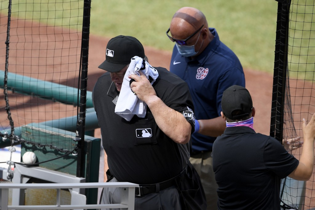 Home plate umpire Joe West, left, leaves the field after he was injured during the first inning of a baseball game between the Toronto Blue Jays and t...