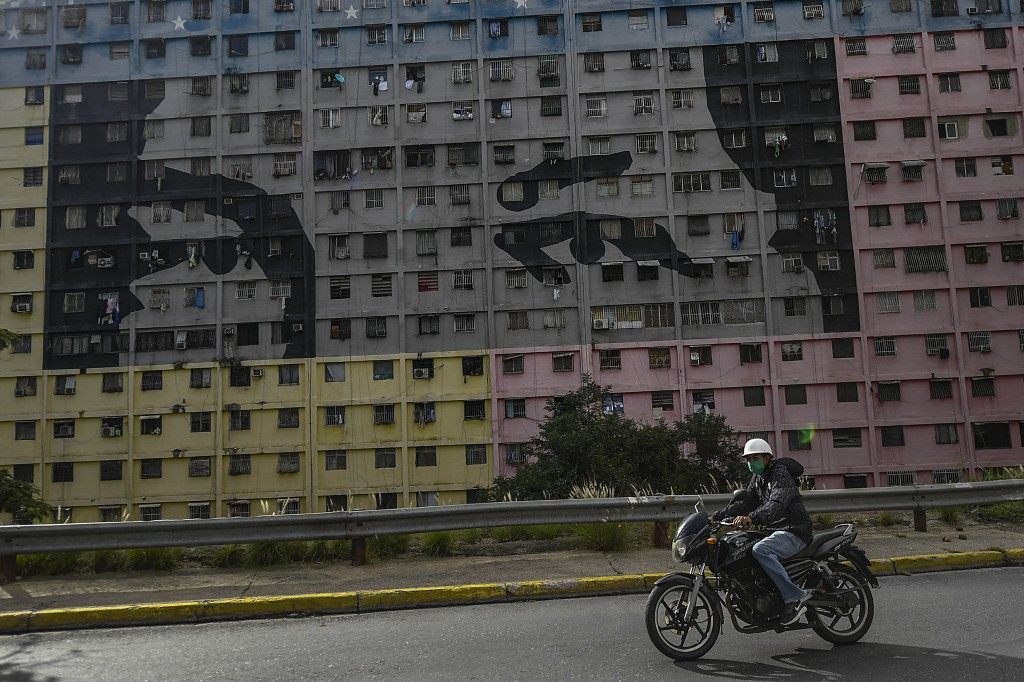 """A biker wearing a protective face mask rides past a mural depicts """"Chavez's eyes"""" a design based on the eyes of the late Venezuelan President Hugo Cha..."""
