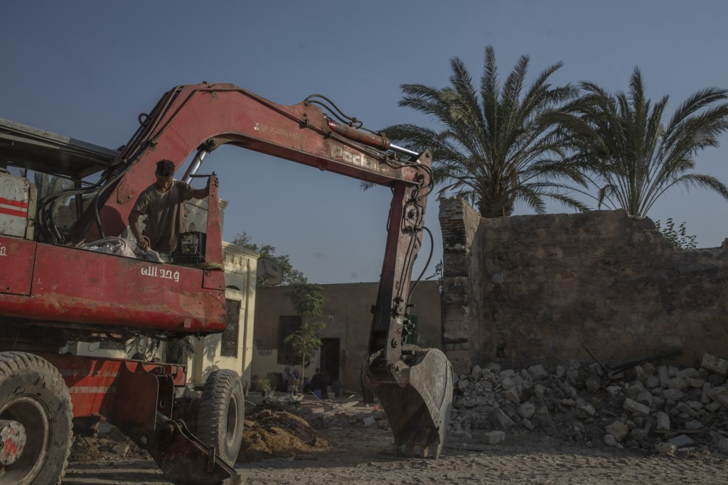Construction workers knock down walls of family mausoleums to clear way for a new highway running through the historic Northern Cemetery in Cairo, Egy...
